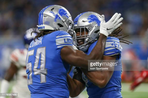 Detroit Lions linebacker Steve Longa celebrates with teammate Detroit Lions linebacker Jalen Reeves-Maybin after a play during a regular season game...