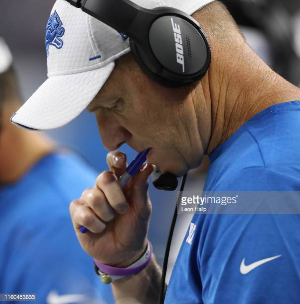 Detroit Lions Offensive Coordinator Darrell Bevell looks over the play book during the third quarter of the preseason game against the New England...
