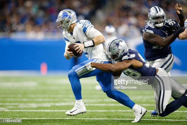 Detroit Lions quarterback Jeff Driskel runs with the ball while trying to avoid being sacked by Dallas Cowboys defensive end Robert Quinn during a...