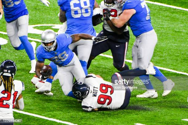 Detroit Lions running back Adrian Peterson runs through the line with Houston Texans defensive end J.J. Watt making the tackle during the Detroit...