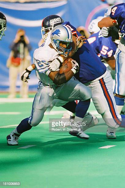 Detroit Lions running back Barry Sanders breaks a tackle while rushing against the New York Giants in New Brunswick NJ 1996