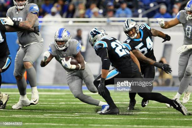 Detroit Lions running back Kerryon Johnson runs the ball under the pressure of Carolina Panthers strong safety Eric Reid during the first half of an...