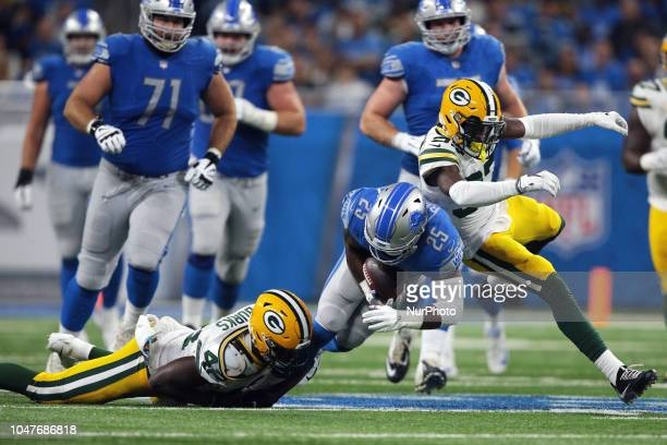 Detroit Lions running back Theo Riddick is tackled by Green Bay Packers linebacker Oren Burks during the first half of an NFL football game in...