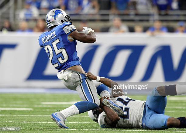Detroit Lions running back Theo Riddick is tackled by Tennessee Titans free safety Daimion Stafford during the fourth quarter of an NFL football game...