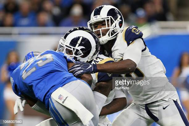 Detroit Lions running back Theo Riddick is taken down by Los Angeles Rams strong safety John Johnson and Los Angeles Rams inside linebacker Cory...