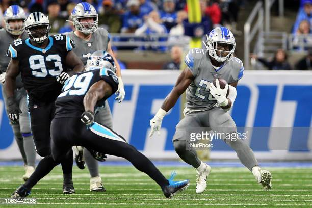 Detroit Lions running back Theo Riddick runs the ball under the pressure of Carolina Panthers free safety Mike Adams during the second half of an NFL...