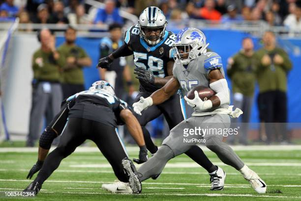 Detroit Lions running back Theo Riddick runs the ball under the pressure of Carolina Panthers outside linebacker Thomas Davis and Carolina Panthers...