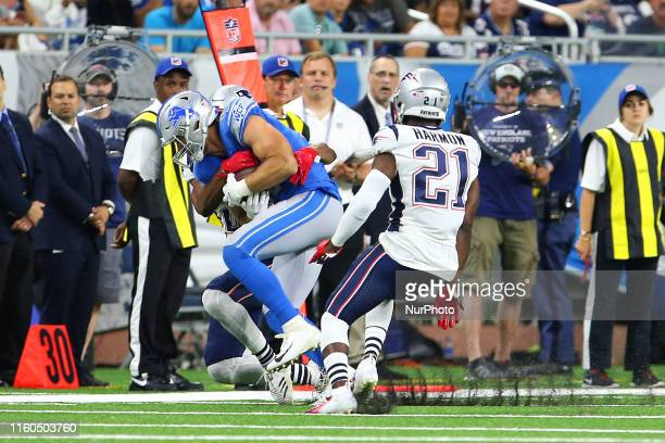 Detroit Lions tight end Jesse James carries the ball under the pressure of New England Patriots defensive back Obi Melifonwu and defensive back Duron...