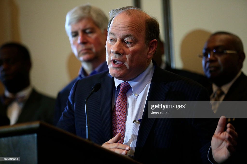 Detroit Mayor Mike Duggan (C), speaks as Michigan Governor Rick Snyder (L), speaks during a news conference November 7, 2014 in Detroit, Michigan. Today U.S. Bankruptcy Judge Steven Rhodes gave the City of Detroit the okay to plan an exit strategy from Chapter 9 Bankruptcy.