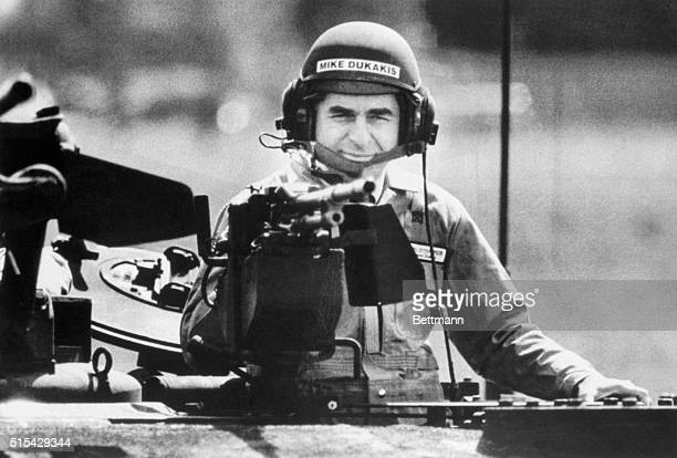 Presidential candidate Mike Dukakis wearing an army tanker's helmet peers behind the loader's weapon of an MIAI Abrams Main Battle Tank during a...