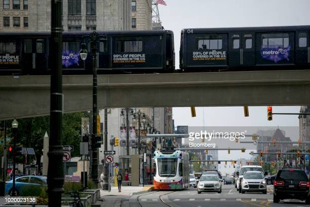 A Detroit People Mover fully automated light rail train travels above a QLine Woodward Avenue streetcar in Detroit Michigan US on Tuesday Aug 14 2018...