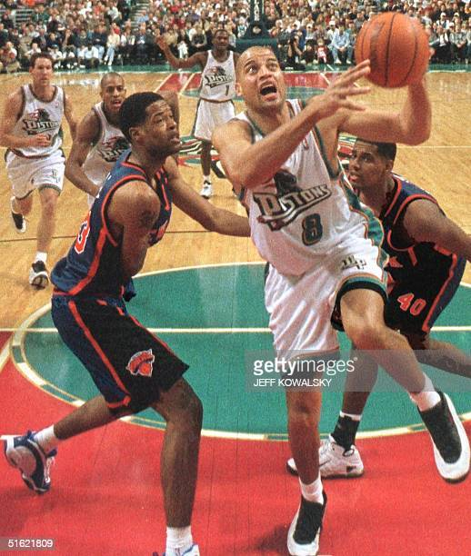 Detroit Piston Bison Dele puts up a shot in the third quarter as New York Knick Marcus Camby and Kurt Thomas defend 28 February at The Palace of...
