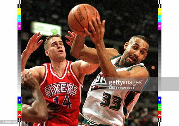 Detroit Piston Grant Hill pulls a rebound away from Philadelphia 76ers Mark Hendrickson in the third quarter 25 January at the Palace in Auburn Hills...