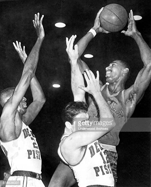 Detroit Piston players Walter Dukes and George Lee can't get high enough to block the Philadelphia Warriors' Wilt Chamberlain's shot Detroit Michigan...