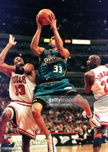 Detroit Pistons forward Grant Hill drives to the basket past Chicago Bulls forward Scottie Pippen and guard Michael Jordan during the third quarter...