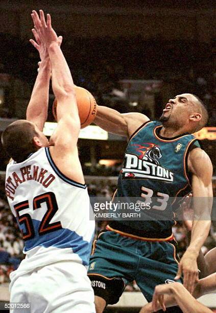 Detroit Pistons forward Grant Hill is stopped short of the basket by Vitaly Potapenko of the Cleveland Cavaliers in the first half of game action 17...