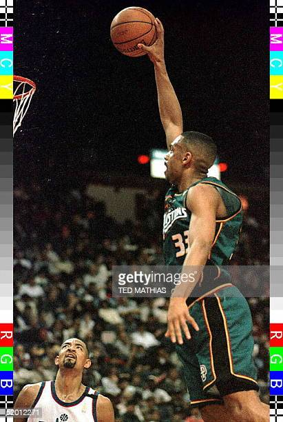 Detroit Pistons' Grant Hill soars to the basket for a dunk in the second quarter as Washington Bullets Juwan Howard looks on in Landover Md 23...