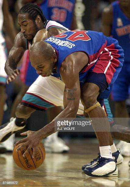 Detroit Piston's Jerry Stackhouse and Memphis Grizzlies' Michael Dickerson go for a loose ball during the first period of their NBA season opener 01...