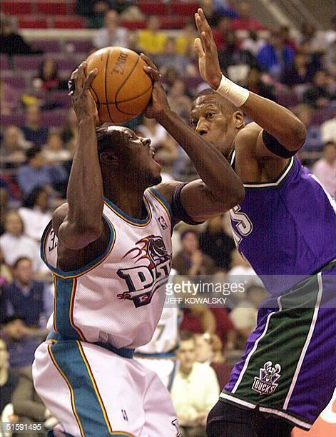 Detroit Pistons' John Wallace puts up a shot over Milwaukee Bucks' Ervin Johnson during the third quarter at the Palace of Auburn Hills Michigan 18...