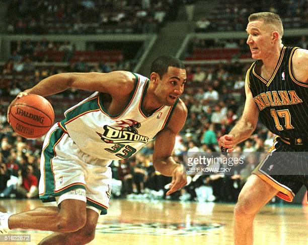 Detroit Pistons player Grant Hill drives around Indiana Pacers player Chris Mullin during the first half of their game 07 February at the Palace of...