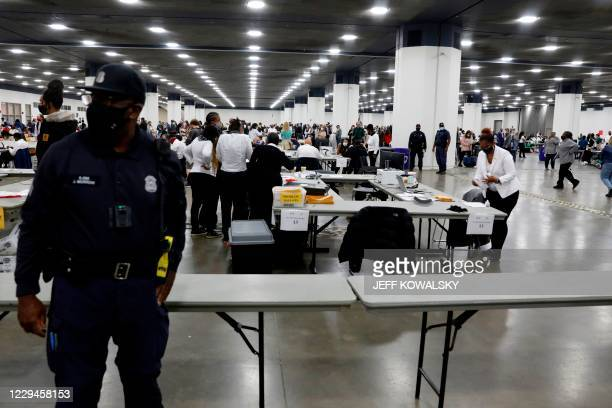 Detroit Police officer stands guard as Detroit election workers work on counting absentee ballots for the 2020 general election at TCF Center on...
