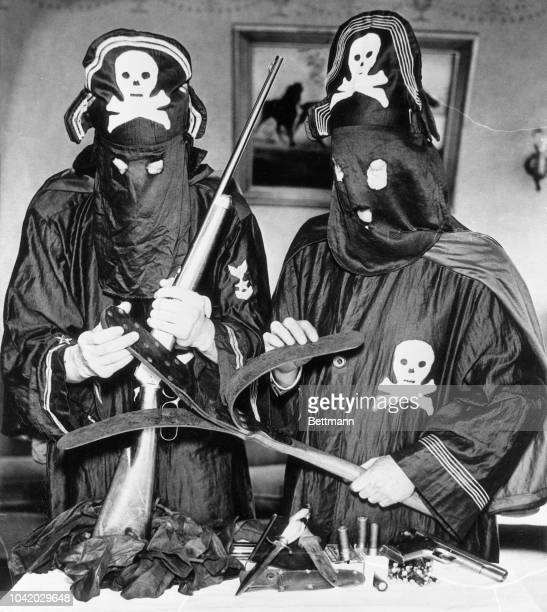 Detroit police officers pose with weapons and regalia seized from Black Legion terrorists The officers dressed in the black robes and pirate hats of...