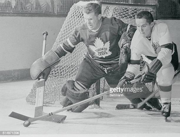 """Detroit Red Wing center Earl """"Dutch"""" Reibel out sticks Toronto Maple Leaf goalie Harry Lumley to grab the puck from the Leaf netman in the closing..."""