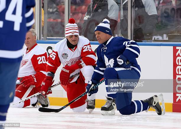 Detroit Red Wings alumni Darren McCarty talks with Toronto Maple Leafs alumni Tie Domi during the 2017 Rogers NHL Centennial Classic Alumni Game at...