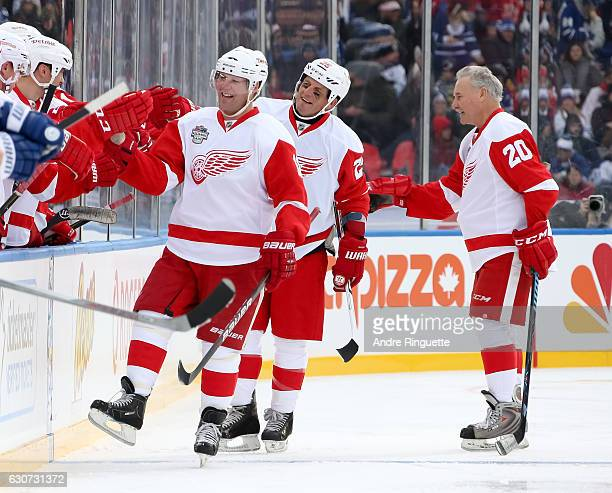 Detroit Red Wings alumni Kirk Maltby celebrates at the bench with Darren McCarty and Mickey Redmond after a goal on Toronto Maple Leafs alumni during...