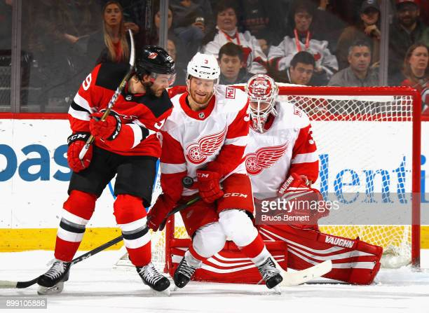 Detroit Red Wings defenseman Nick Jensen takes the puck in the midsection while defending against New Jersey Devils center Brian Gibbons during the...