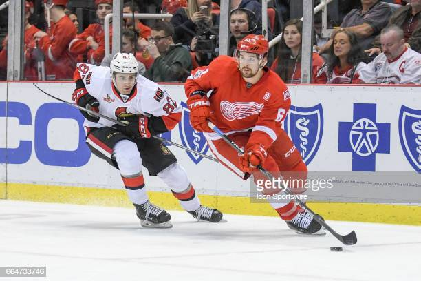 Detroit Red Wings defenseman Xavier Ouellet brings the puck up ice followed by Ottawa Senators center Colin White during the NHL hockey game between...
