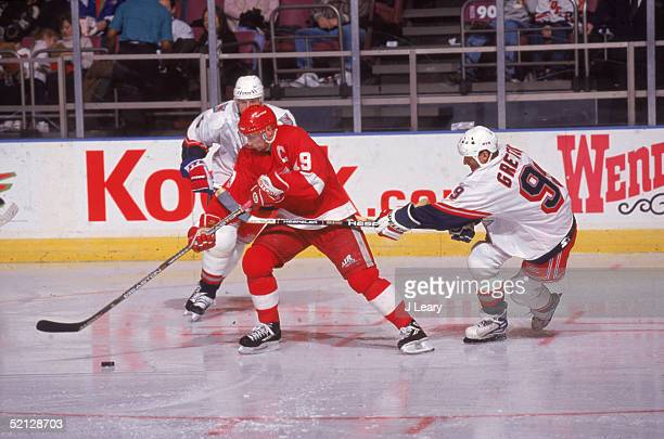 Detroit Red Wings forward and captain Steve Yzerman controls the puck as New York Rangers forward Wayne Gretzky checks him during a game hosted by...