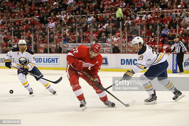 Detroit Red Wings forward Andreas Athanasiou and Buffalo Sabres defenseman Jake McCabe chase after the puck during the first period of a regular...