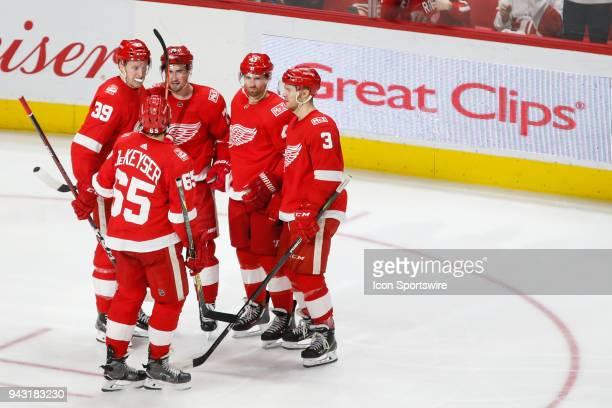 Detroit Red Wings forward Dylan Larkin is congratulated by teammates forward Anthony Mantha forward Darren Helm defenseman Nick Jensen and defenseman...