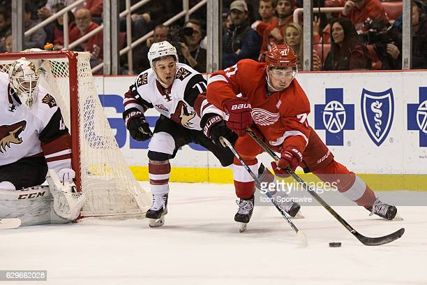 Detroit Red Wings forward Dylan Larkin skates around the net with the puck against Arizona Coyotes defenseman Anthony DeAngelo during the third...