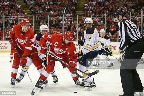 Detroit Red Wings forward Henrik Zetterberg of Sweden and Buffalo Sabres forward Evander Kane battle for control of the puck during a faceoff during...