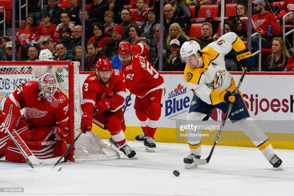 Detroit Red Wings goalie Jimmy Howard (35) guards the corner of the goal while Detroit Red Wings defenseman Nick Jensen (3) and Detroit Red Wings forward Frans Nielsen, of Denmark, (51) defend against Nashville Predators forward Filip Forsberg, of Sweden, (9) during the third period of a regular season NHL hockey game between the Nashville Predators and the Detroit Red Wings on February 20, 2018, at Little Caesars Arena in Detroit, Michigan. Nashville defeated Detroit 3-2.