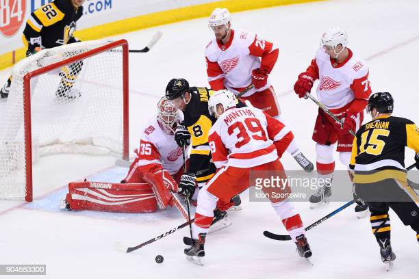 Detroit Red Wings Goalie Jimmy Howard keeps the puck out of the net with Pittsburgh Penguins Defenseman Brian Dumoulin in front as Detroit Red Wings...
