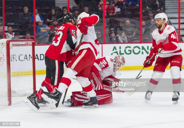 Detroit Red Wings Goalie Jimmy Howard makes a glove save in the first period asOttawa Senators Right Wing Jack Rodewald battles for position in front...