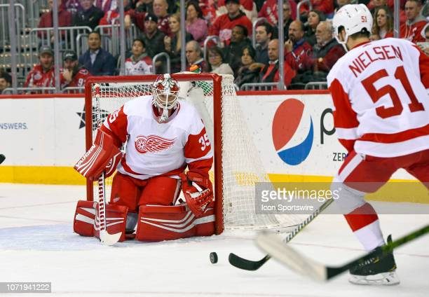 Detroit Red Wings goaltender Jimmy Howard makes a second period save as center Frans Nielsen skates in for the puck against the Washington Capitals...