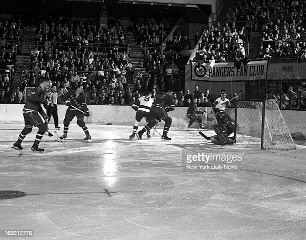 Detroit Red Wings Gordie Howe is wide with his shot as New York Ranger Jim Nielson rides him off at Garden Blues' goalie Jacques Plante moves in...