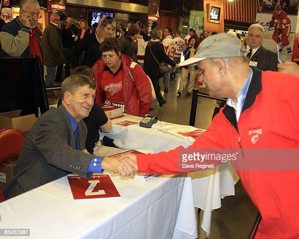 Detroit Red Wings Hall of Famer Ted Lindsay signs copies of his book for fans in the concorse on Breast Cancer Awareness Night during a NHL game...