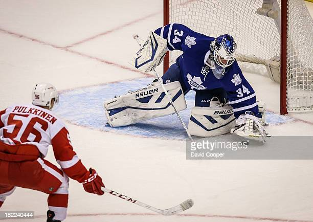 Detroit Red Wings left wing Teemu Pulkkinen heads for the net to give Toronto Maple Leafs goalie James Reimer a snow shower as Reimer covers the puck...