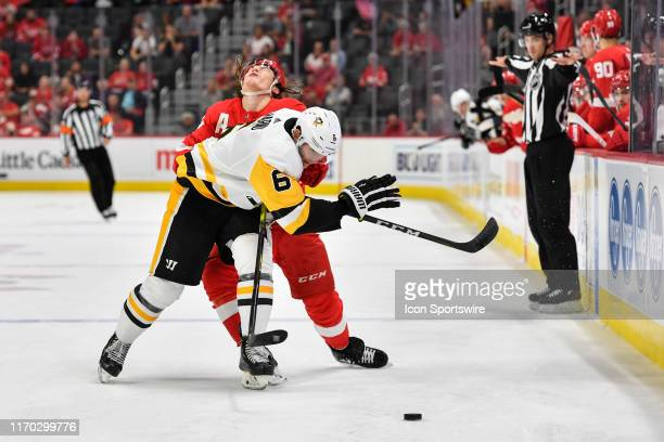 Detroit Red Wings left wing Tyler Bertuzzi takes a hit from Pittsburgh Penguins defenseman John Marino as they battle for possession during the...