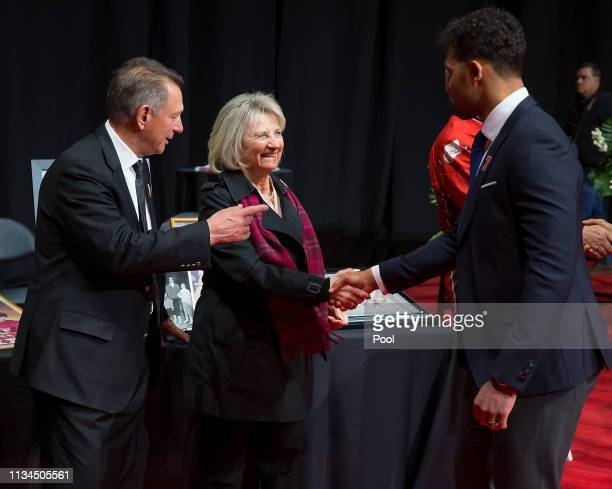 Detroit Red Wings owner Marian Ilitch and General Manager Ken Holland talk to Trevor Daley during the public visitation of NHL Hall of Famer and...