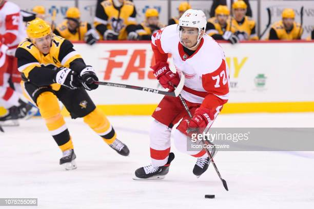 Detroit Red Wings Winger Andreas Athanasiou skates with the puck in front of Pittsburgh Penguins Center Evgeni Malkin during the first period in the...