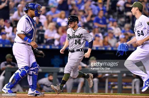 Detroit Tigers' Alex Presley scores between Kansas City Royals catcher Salvador Perez and relief pitcher Matt Strahm on a tworun single by Miguel...
