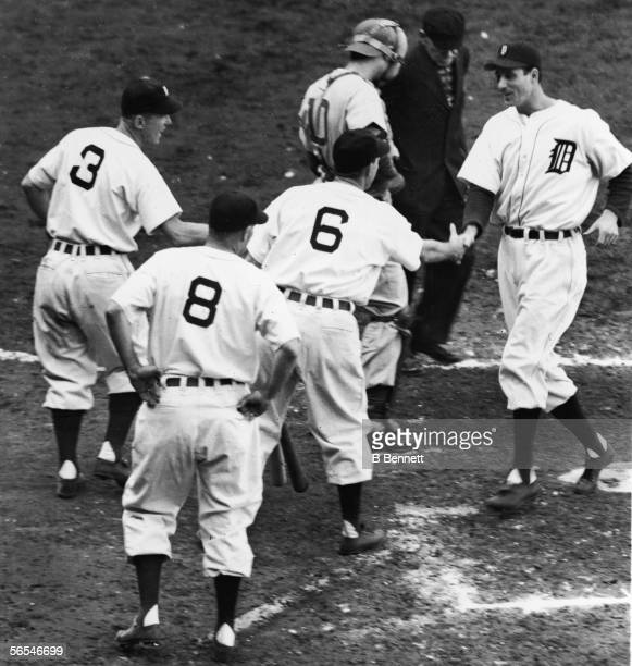 Detroit Tigers batter Hank Greenberg is congratulated by teammate Roy Cullenbine the next batter up as he crosses home plate after hitting a homerun...