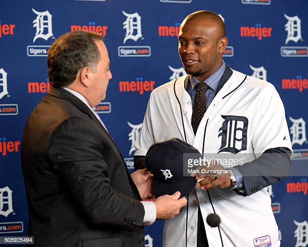 Detroit Tigers Executive Vice President of Baseball Operations and General Manager Al Avila hands a baseball hat to newest Tiger Justin Upton during...