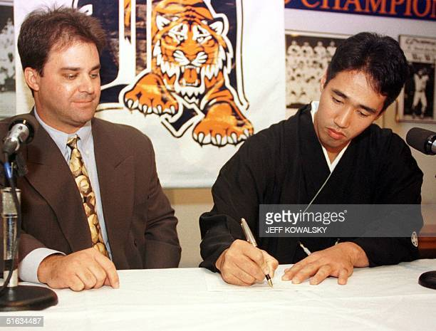 Detroit Tigers' General Manager Randy Smith watches Masao Kida 09 December sign a contract in Detroit MI to play for the team Kida a righthanded...